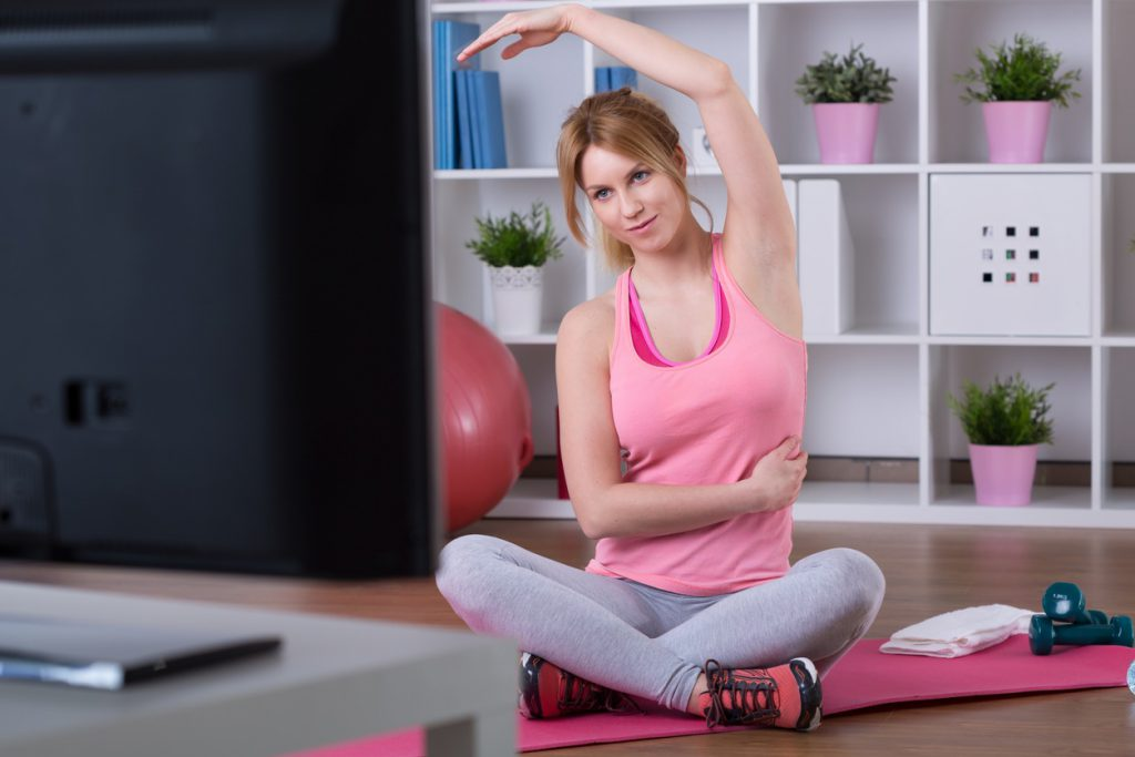 Mujer joven con ropa deportiva haciendo ejercicio frente a un televisor. Practicar deporte suave es beneficioso para aliviar el dolor de la fibromialgia reumática.